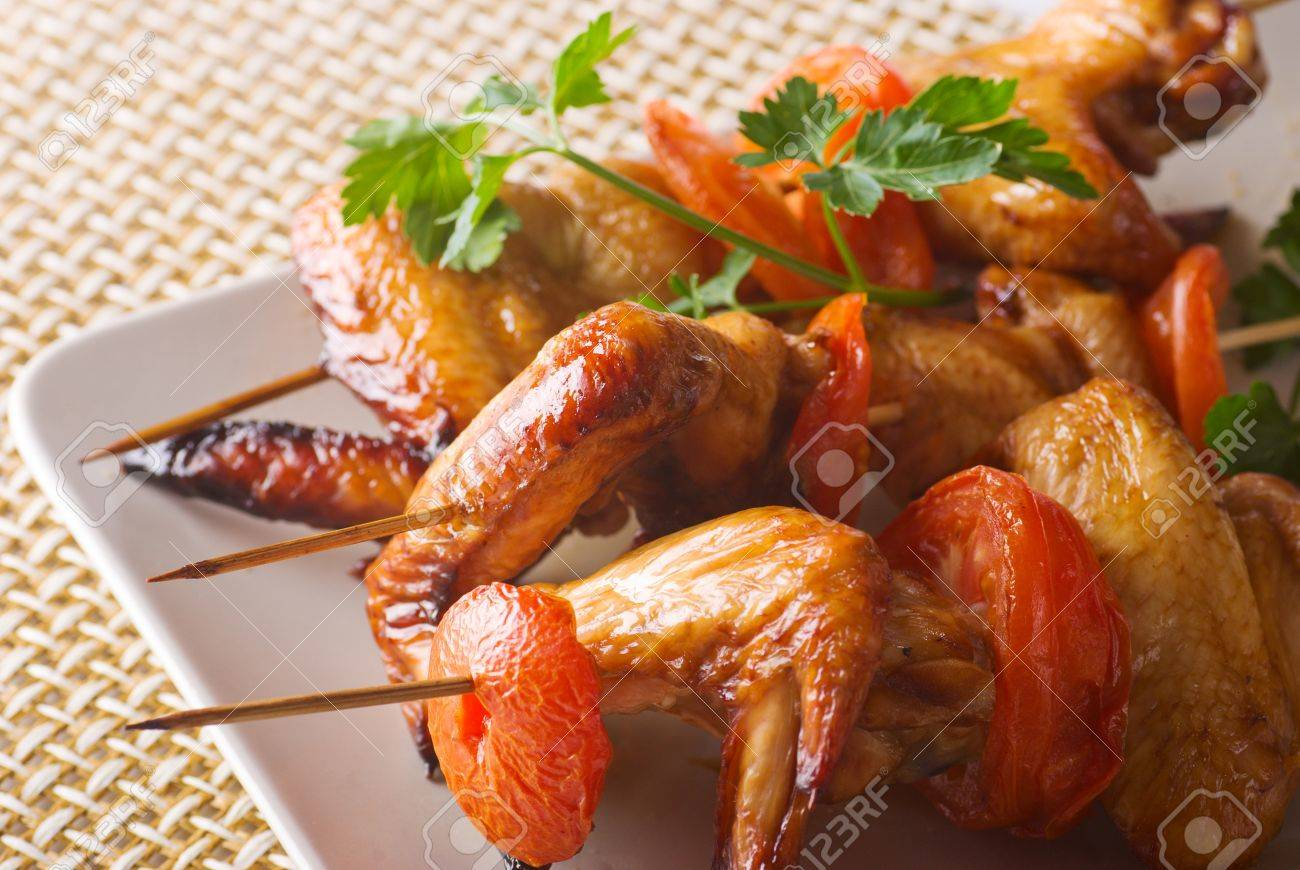 skewers of chicken wings with tomatoes on a plate Stock Photo - 9961083