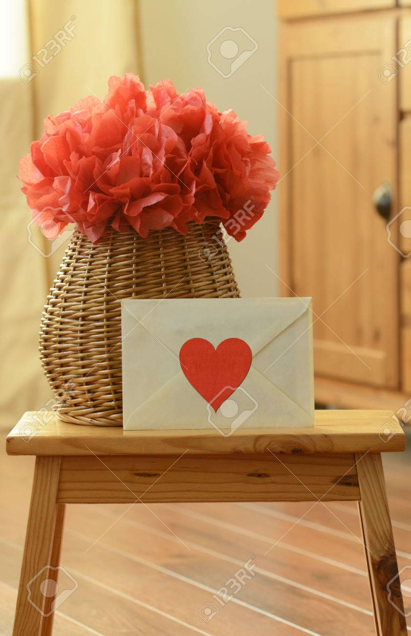 Vase basket with red tissue paper flower pom pom and envelope stock photo vase basket with red tissue paper flower pom pom and envelope with red heart shaped sticker on the small wooden step stool mightylinksfo
