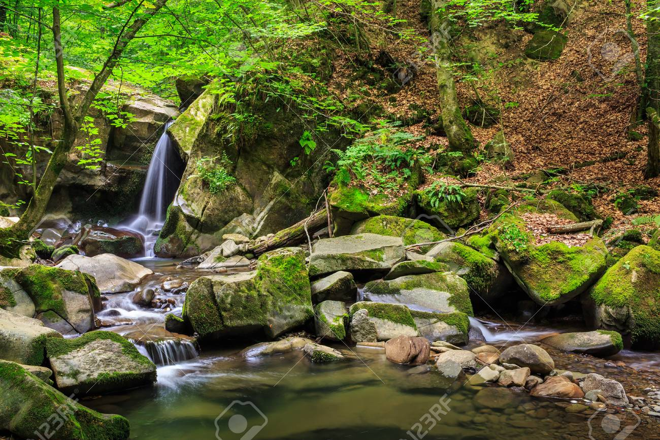 incredibly beautiful and clean little waterfall with several cascades over large stones in the forest comes out of a huge rock covered with moss Stock Photo - 26822130