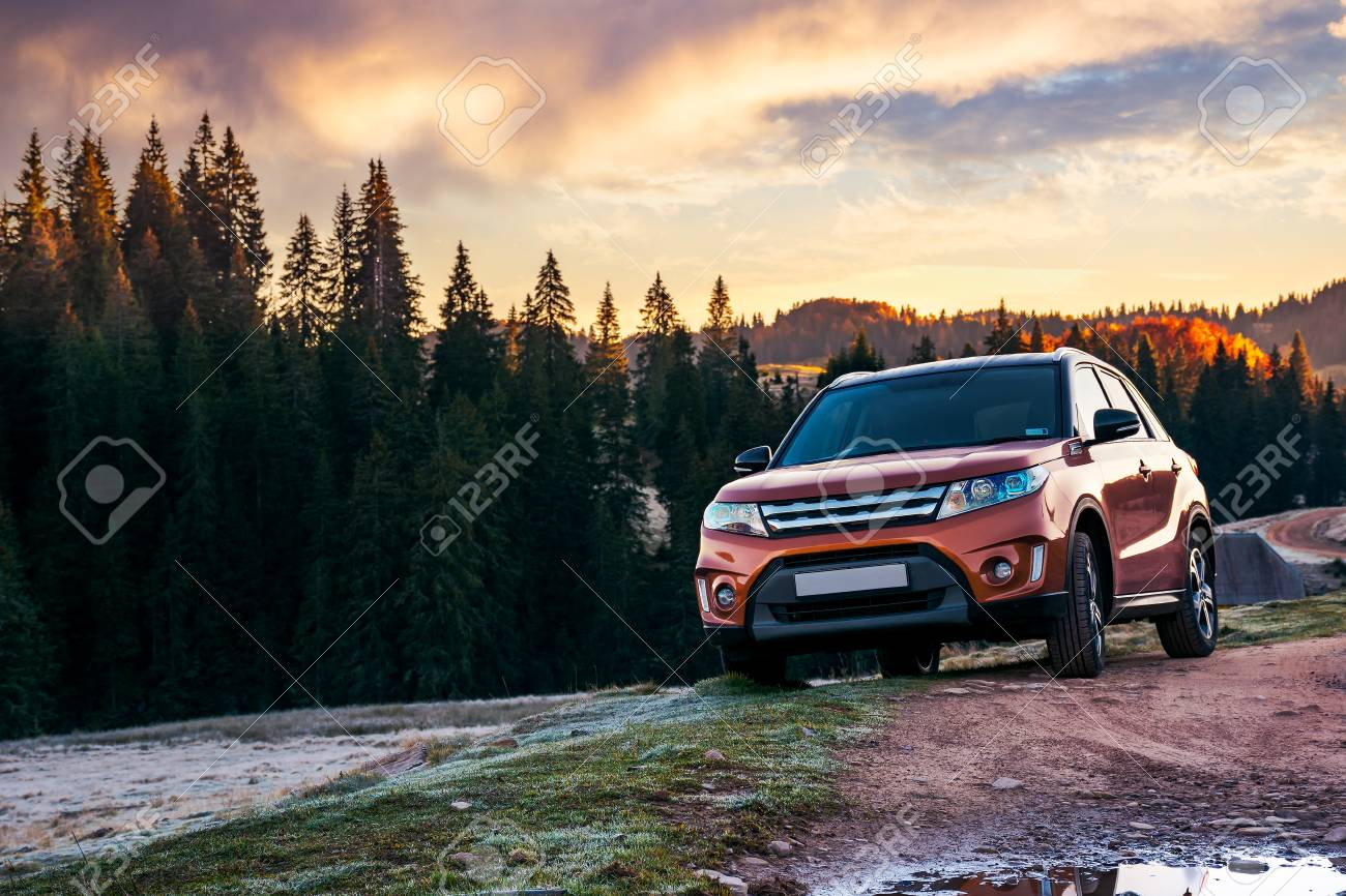 orange 4wd suv parked in mountain at sunrise. beautiful autumn scenery with gravel road through spruce forest. travel Europe by car concept - 108411214