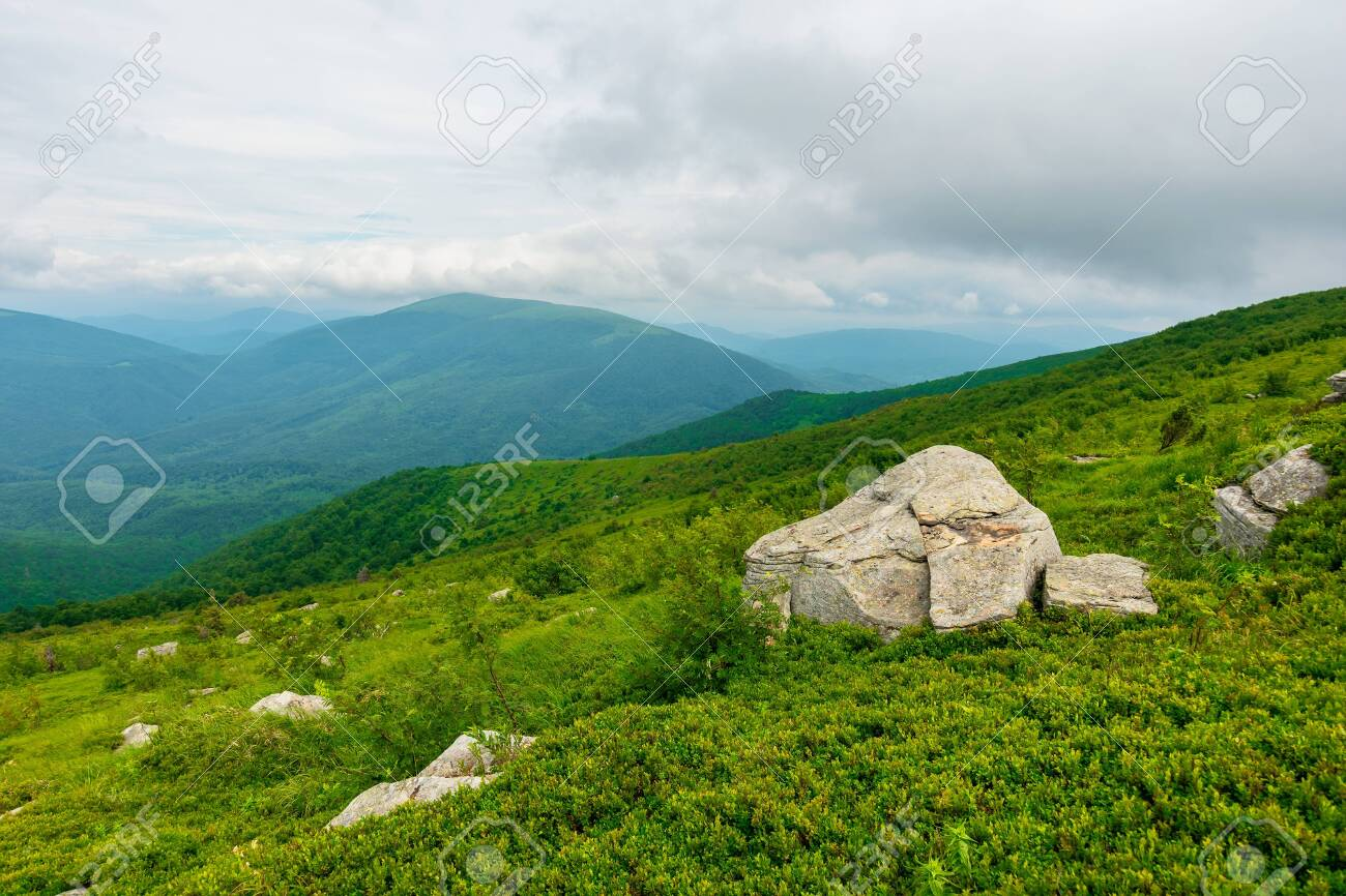 boulders on the alpine hillside. view from the edge of a hill. beautiful summer landscape in mountains. overcast windy weather with grey clouds on the sky - 151738563