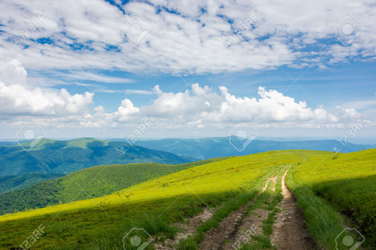 wide trail through grassy meadow. mountain ridge in the distance beneath a gorgeous cloudscape on the blue sky. travel backcountry concept - 168817576