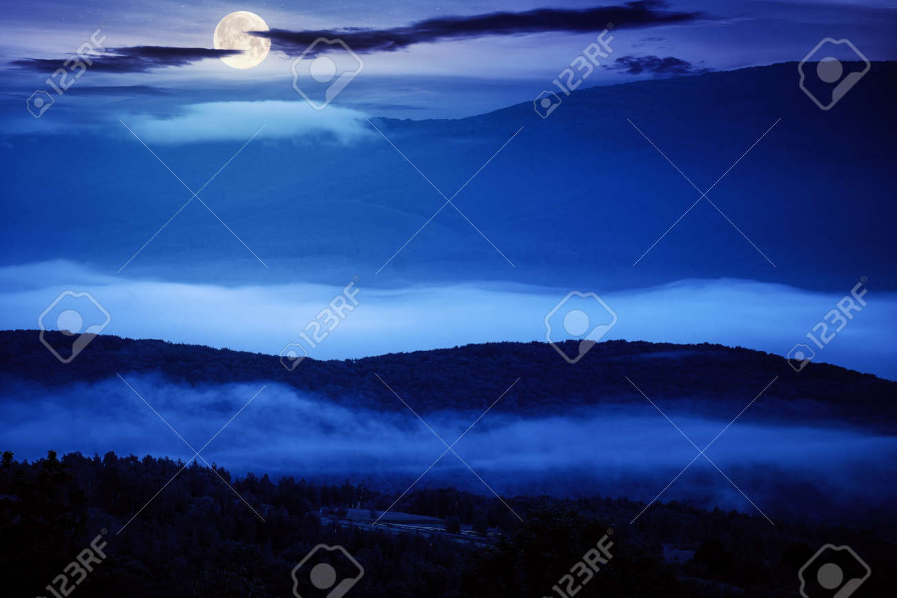 glowing fog in the rural valley at night. beautiful mountain landscape in full moon light. view from the hill - 169791474