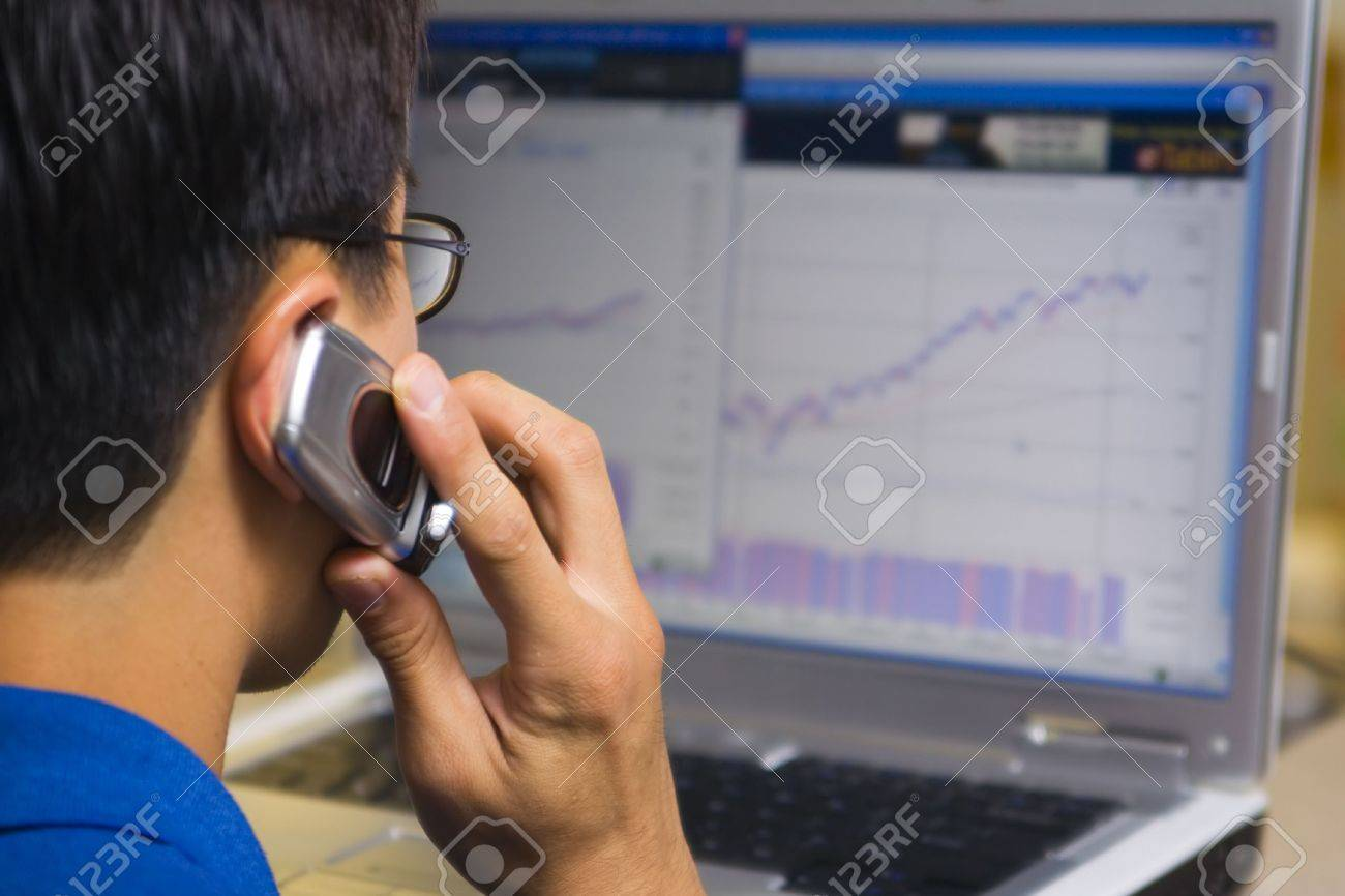stock broker calling his client while looking at computer stock chart Stock Photo - 731748