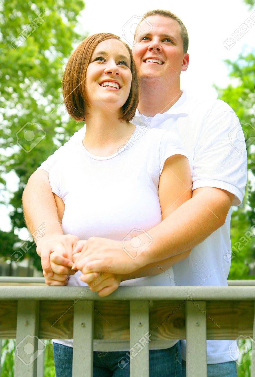 two romantic couple embracing in park, the man hold his wife, both enjoying a view. concept for happiness, love or young Stock Photo - 3287678