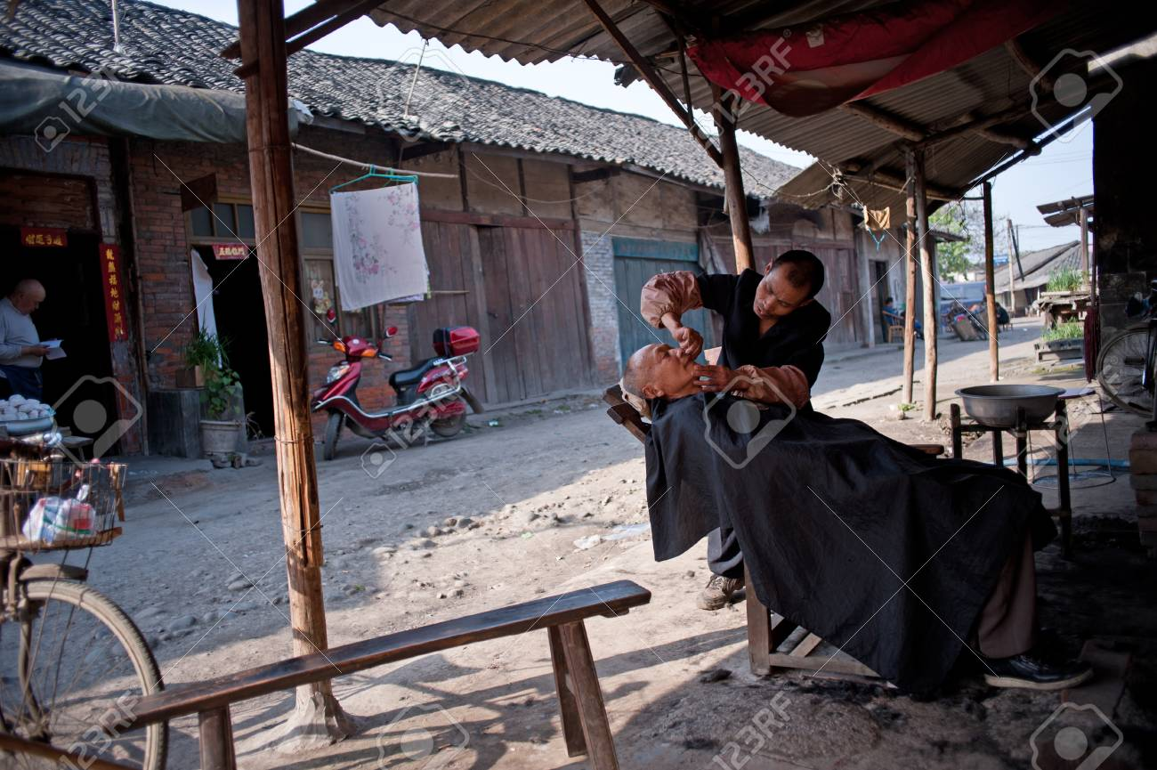 SICHUAN,CHINA-APRIL 4,2010:The nameless barber sitting in his shop, due to loss of arable land, in order to survive, local farmers diverted to do business, Sichuan, China, April 4, 2010 Stock Photo - 12768552
