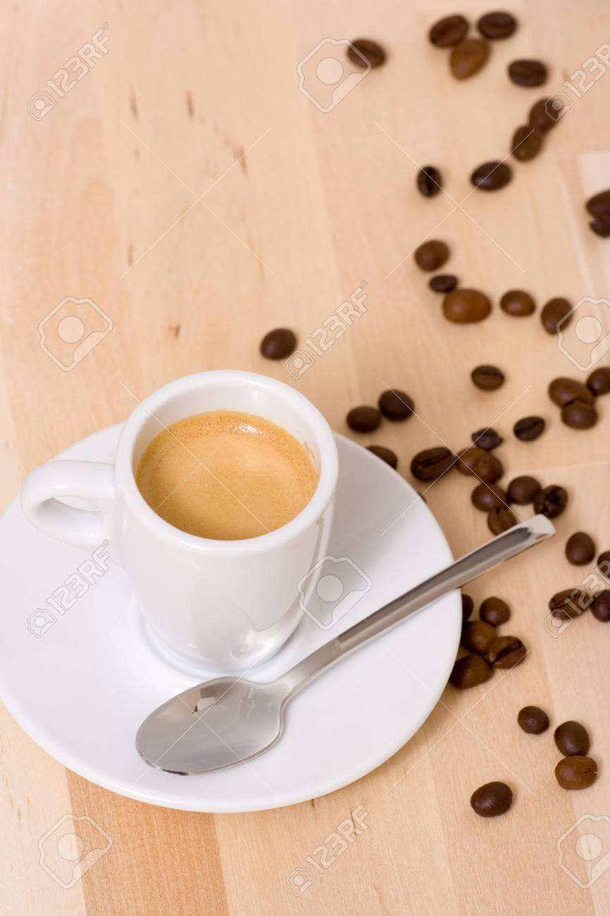 Coffee cup and coffee beans over a wood background Stock Photo - 766245
