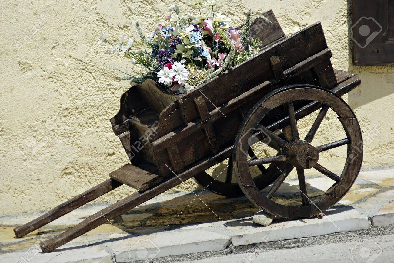 Old small wooden coach full of summer flowers at sunny day. Stock Photo - 9658759