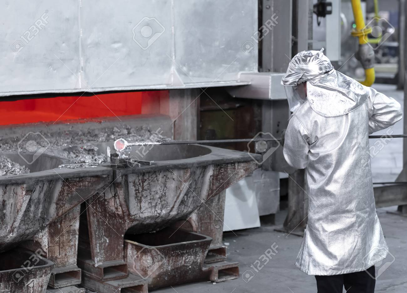 a worker taking a sample of molten aluminum from the inside of