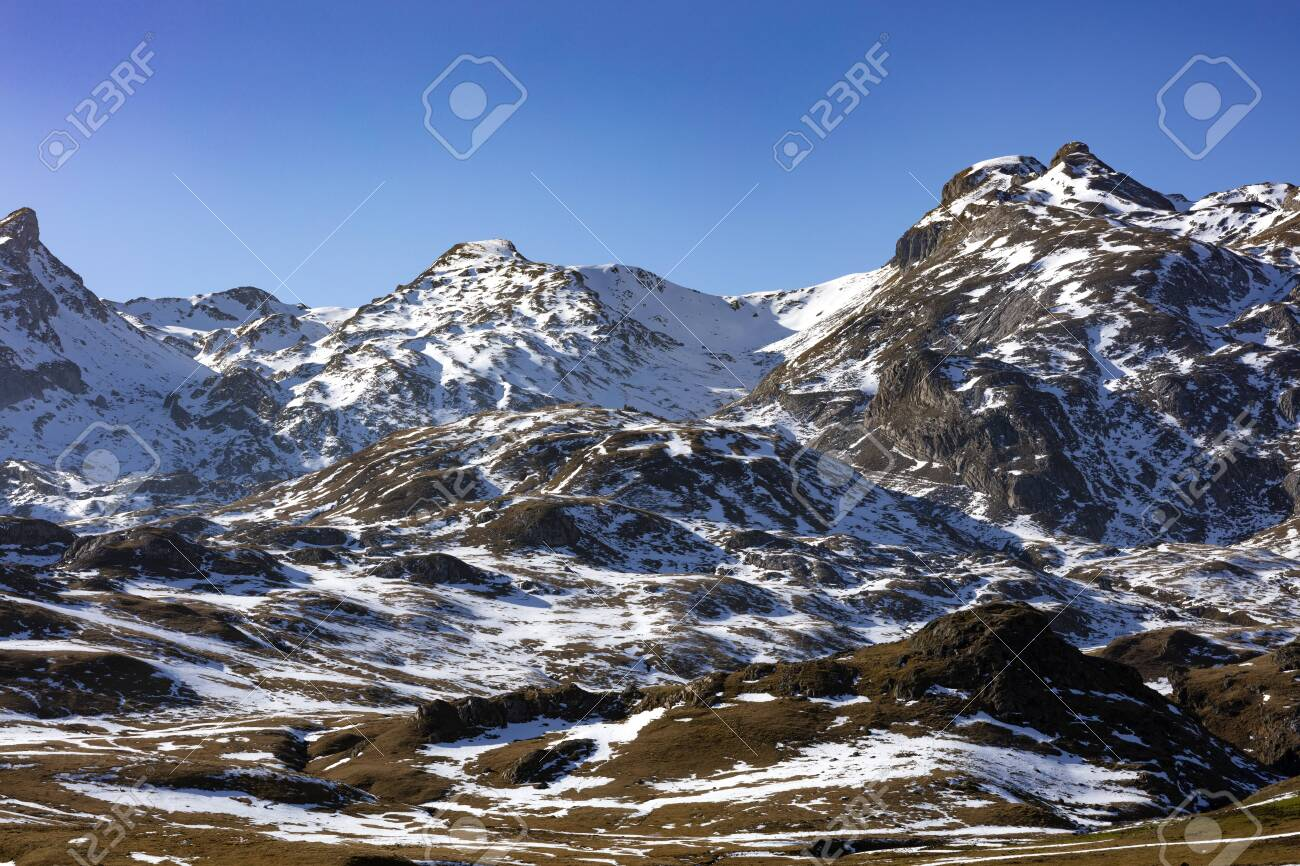 snowy mountains landscape showing the first snow on brown grass during the winter with a blue and clear sky - 116921195