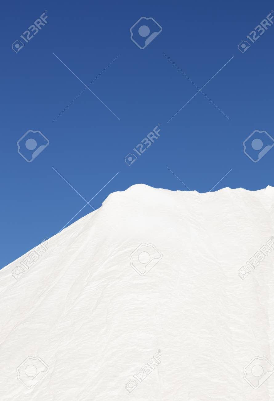 mountain of white salt on blue sky, salt extraction process and piled up before packaging - 116921197