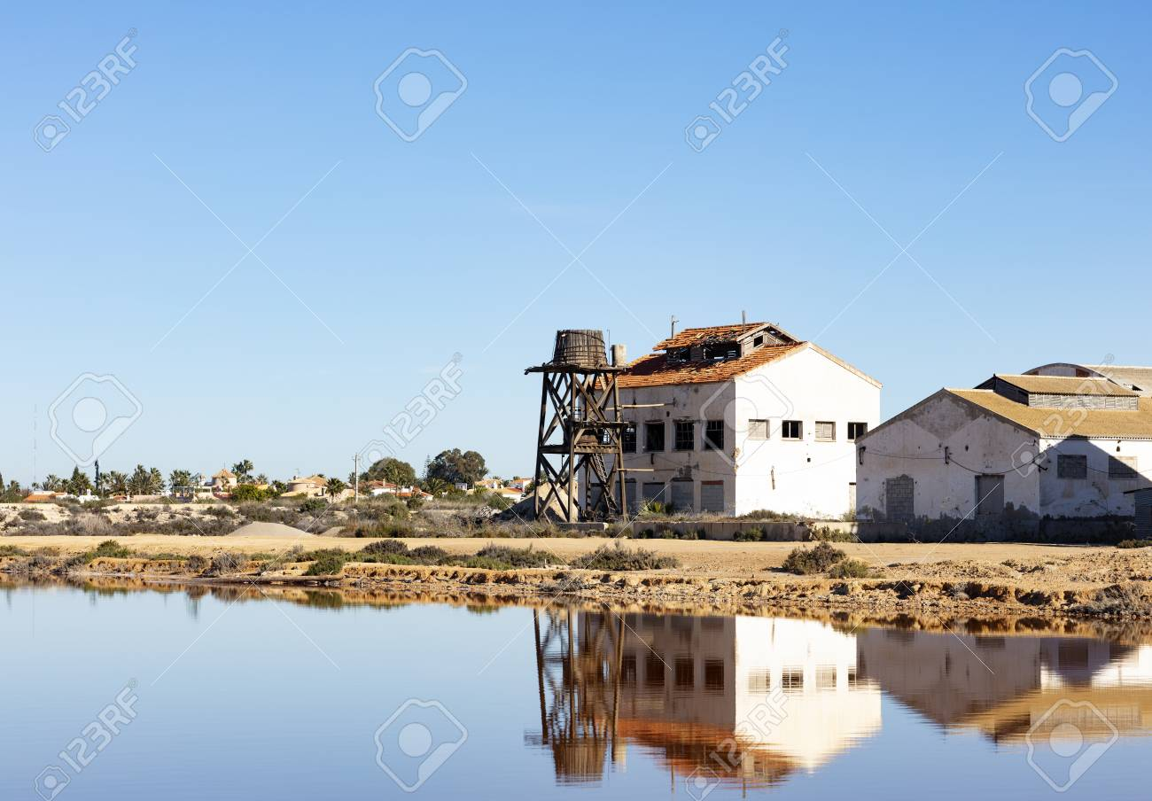 old ruined building with wooden water tank on the edge of a saline lake, both are reflected in the water on the blue background of the sky - 116921200