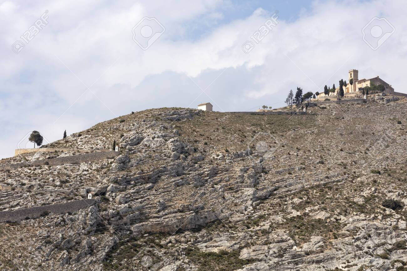 ermitage of saint christ on top of the hill in Bocairent, Spain with the pathway, the hill is rocky and the sky in the background is cloudy - 123523492