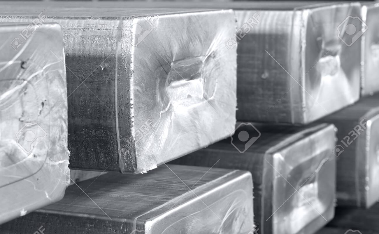 heavy aluminum ingots stacked in a warehouse foundry, raw material to be processed in a hot mill. Photo in black and white with bluish tone - 123523527