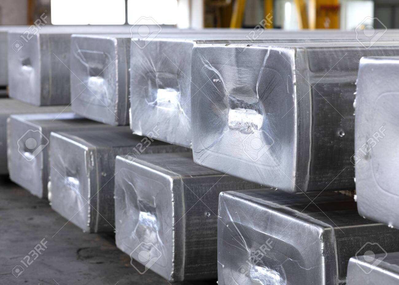heavy aluminum ingots stacked in a warehouse foundry, raw material to be processed in a hot mill - 123523542