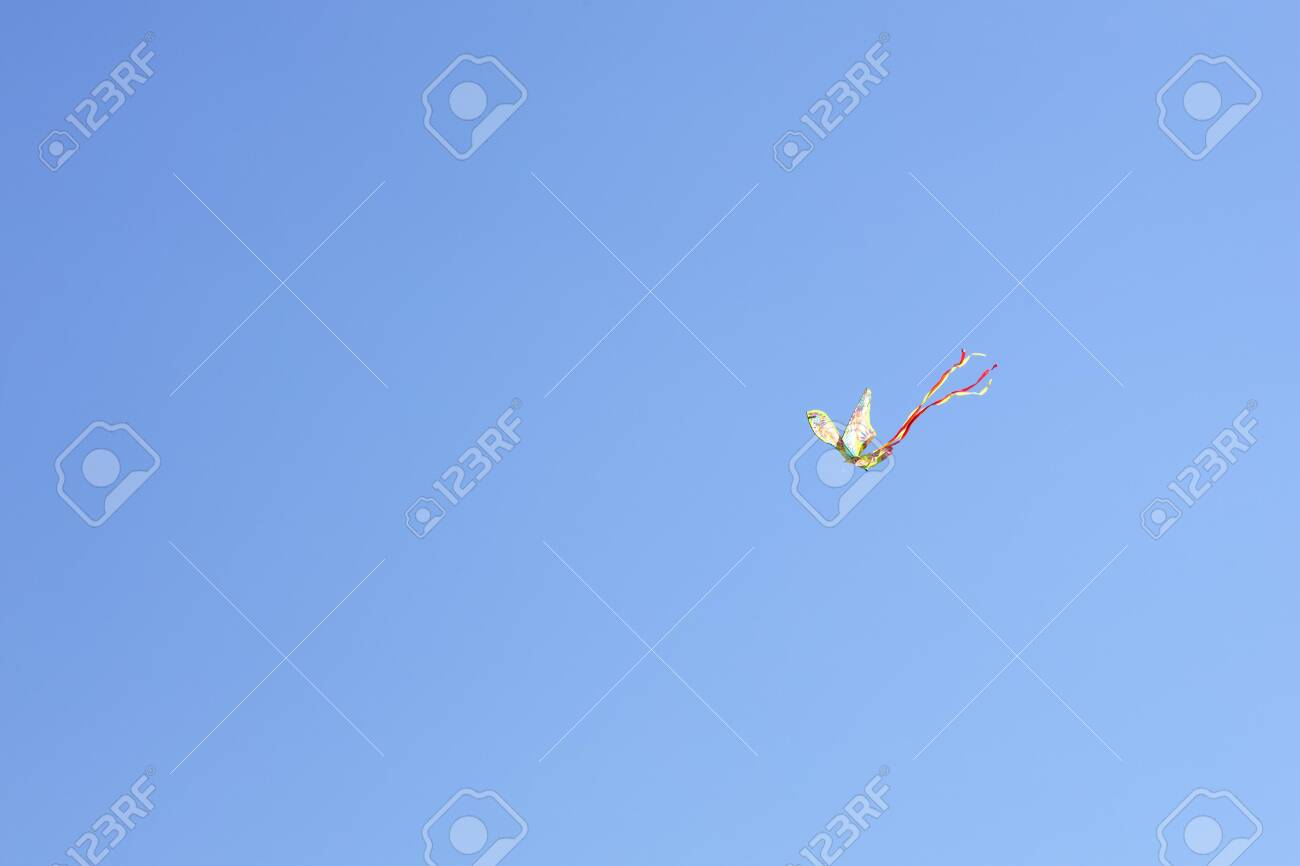 colorful kite flying on a blue sky with red and yellow ribons - 123523569