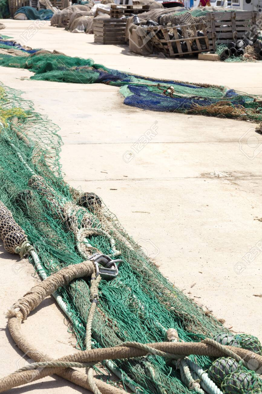 fishing nets extended in the port to be revised, there are blue and green, with wooden boxes in the background - 123523596