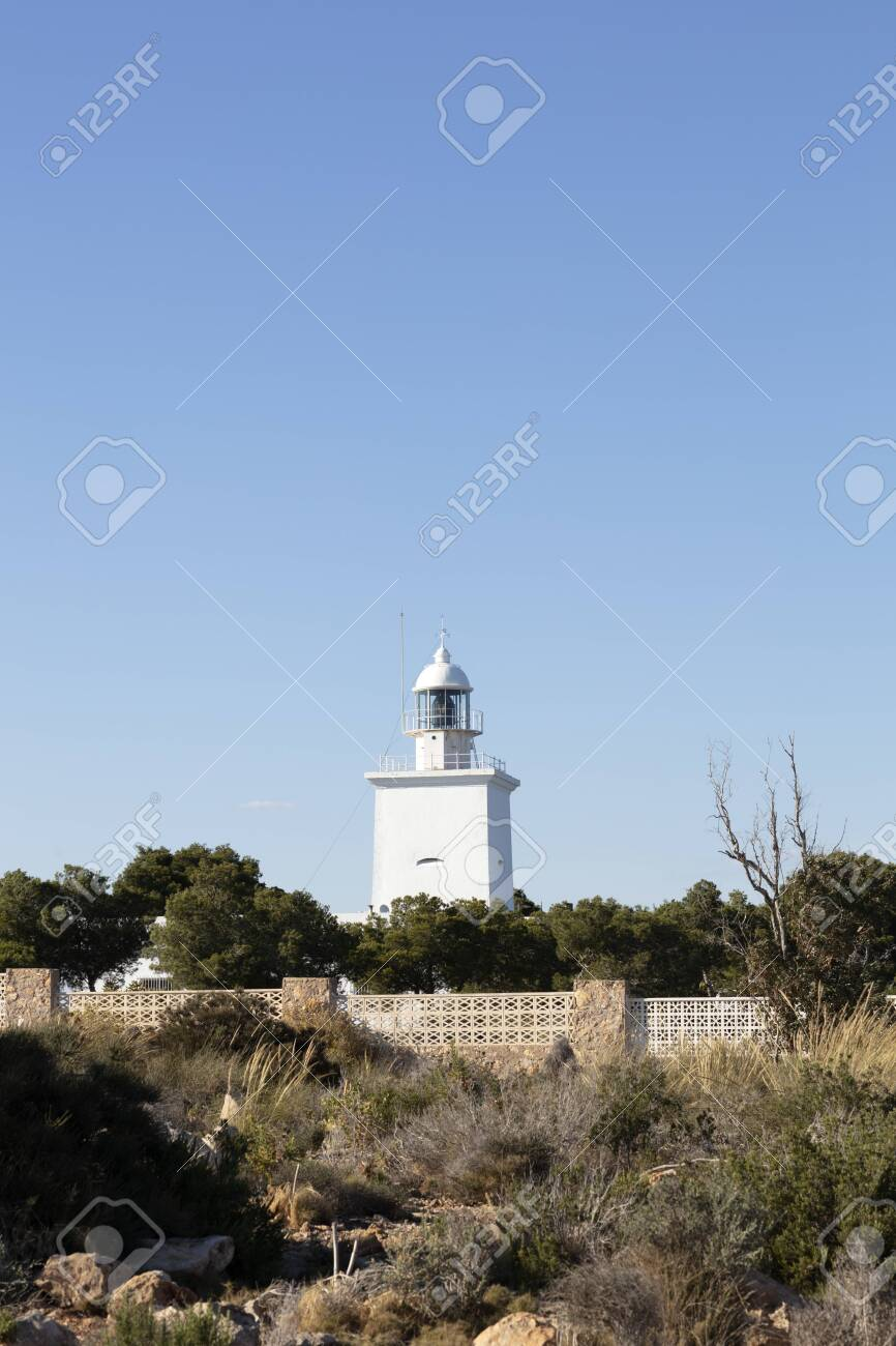white mediterranean lighthouse of Santa Pola with the coast of Alicante in the background - 123523633