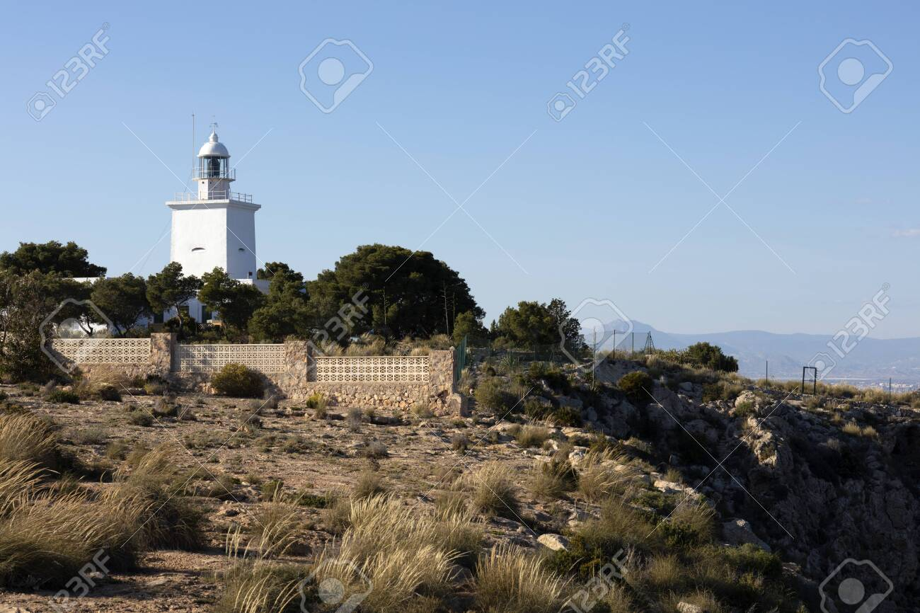 white mediterranean lighthouse of Santa Pola with the coast of Alicante in the background - 123523658