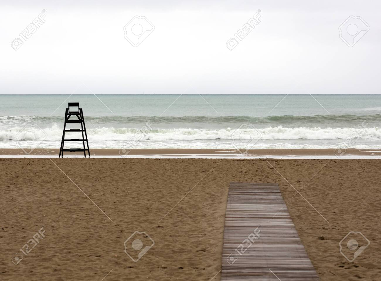 the beach during a cloudy day with a beach watchman chair alone on the sand and a wooden pathway - 123523682