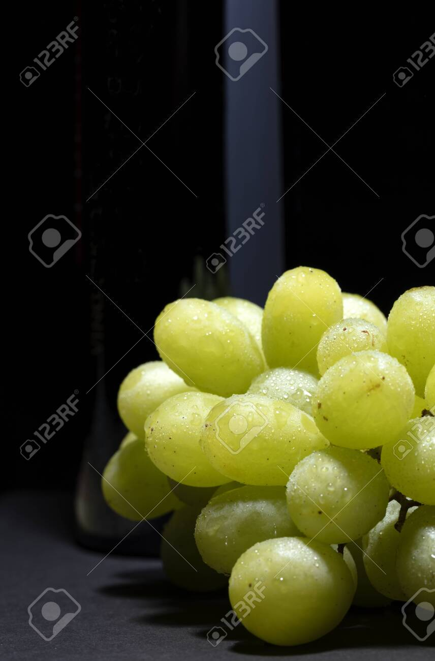 bunch of white grapes with water drops on black background with a light reflection on the bottle - 123523722