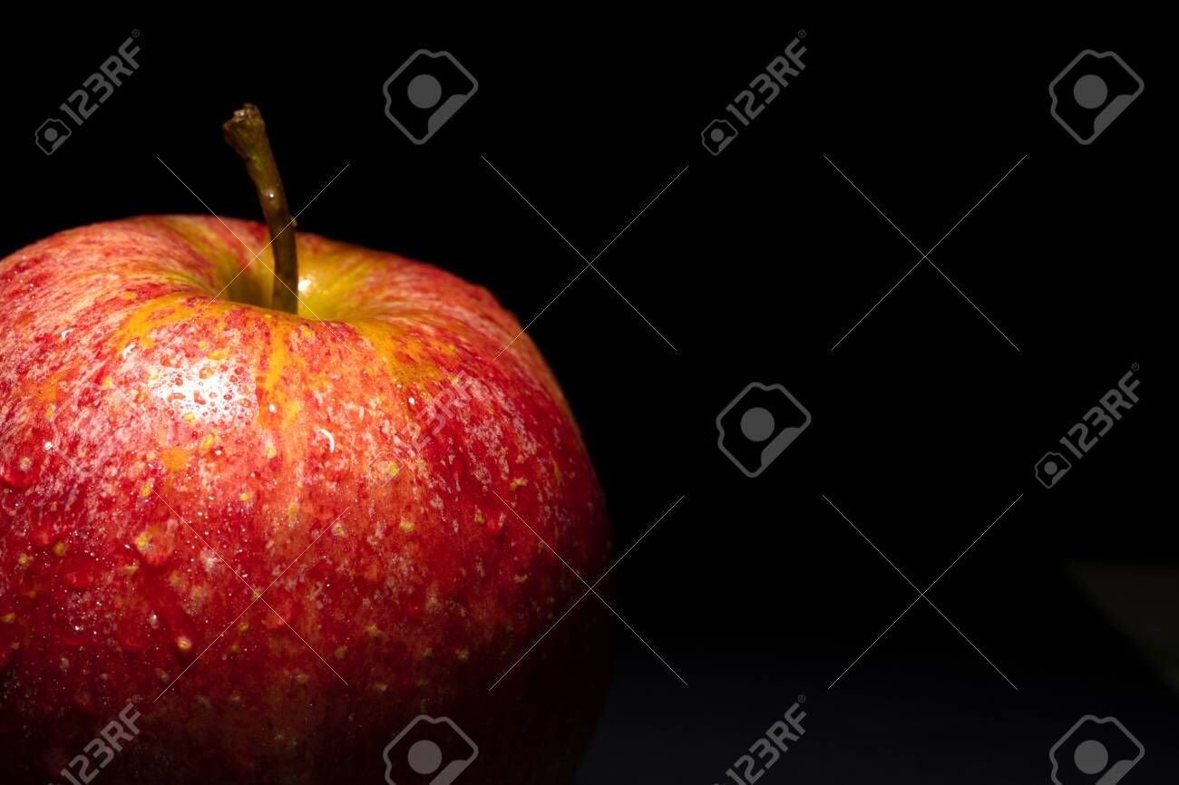 red apple with drops of water on black background, image conveys freshness, free space on the right for text - 123523749