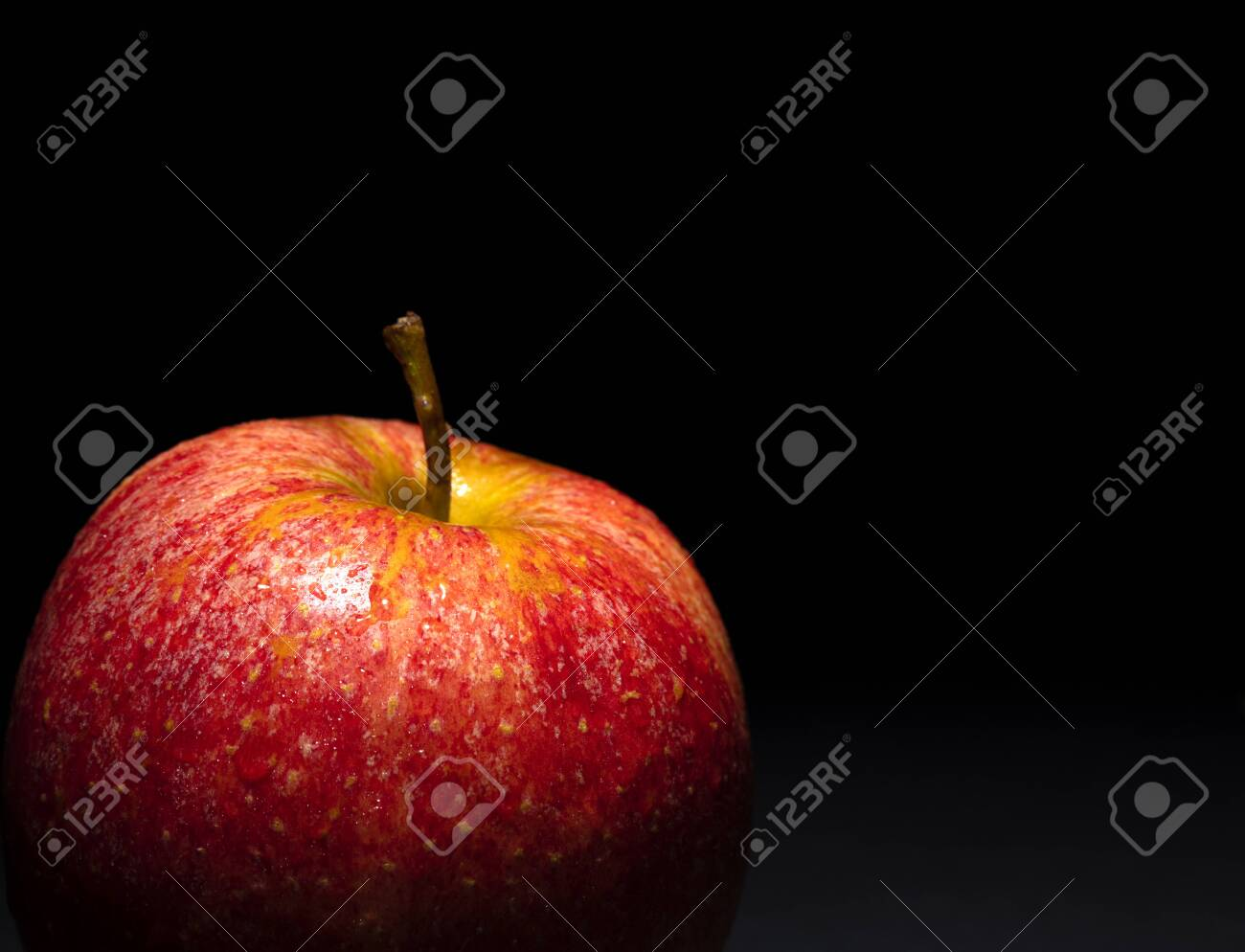 red apple with drops of water on black background, image conveys freshness, free space above for text - 123523751