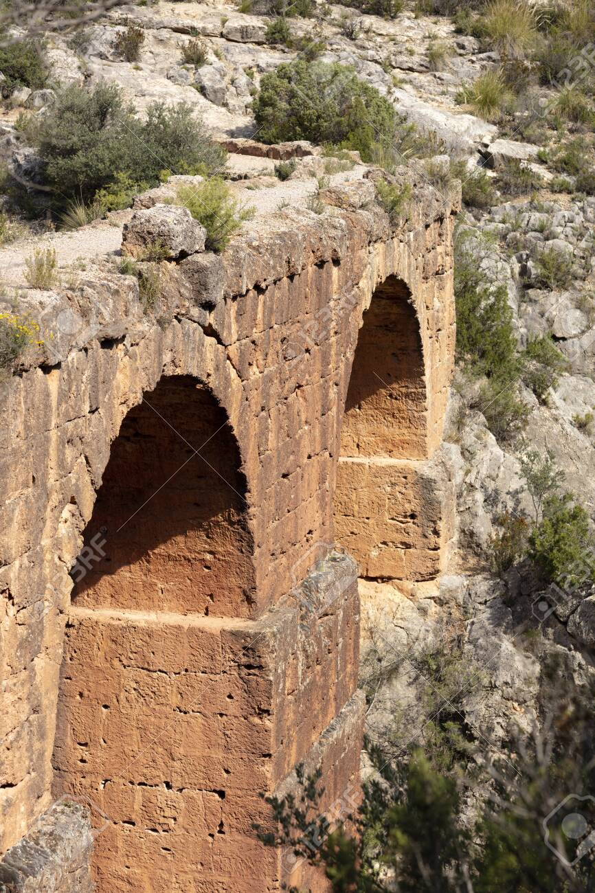Roman aqueduct of the rock cut in Chelva, Valencia, built in the 1st century AC by the romans is one of the most important in Spain - 123523794