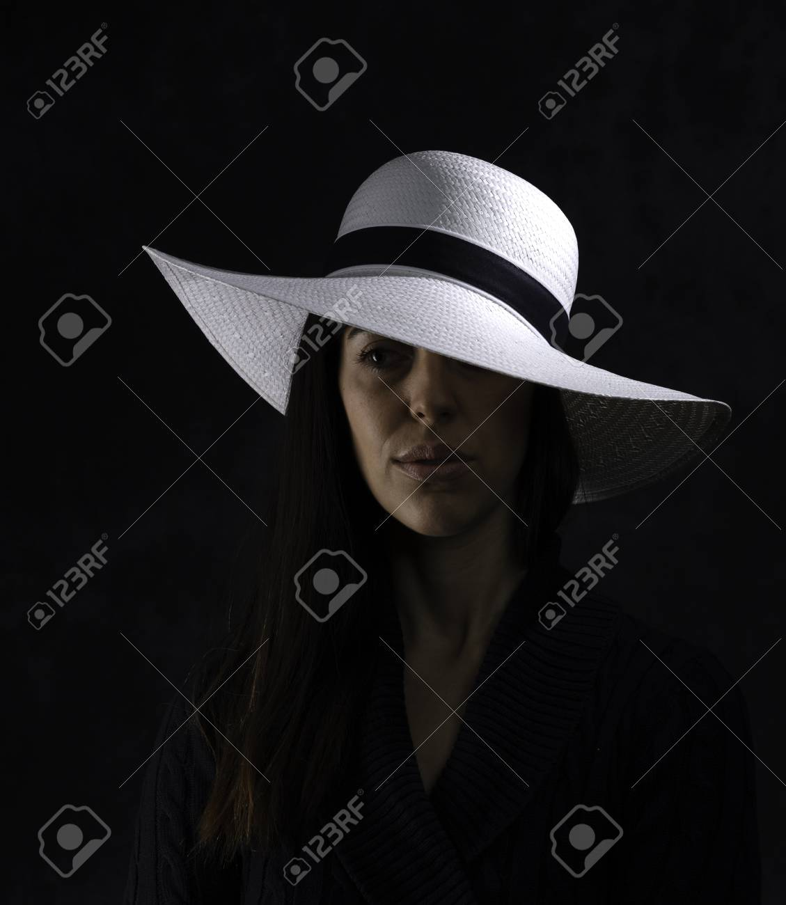 portrait of a beautiful young girl with a white hat on a black background, looking at her side - 126332863