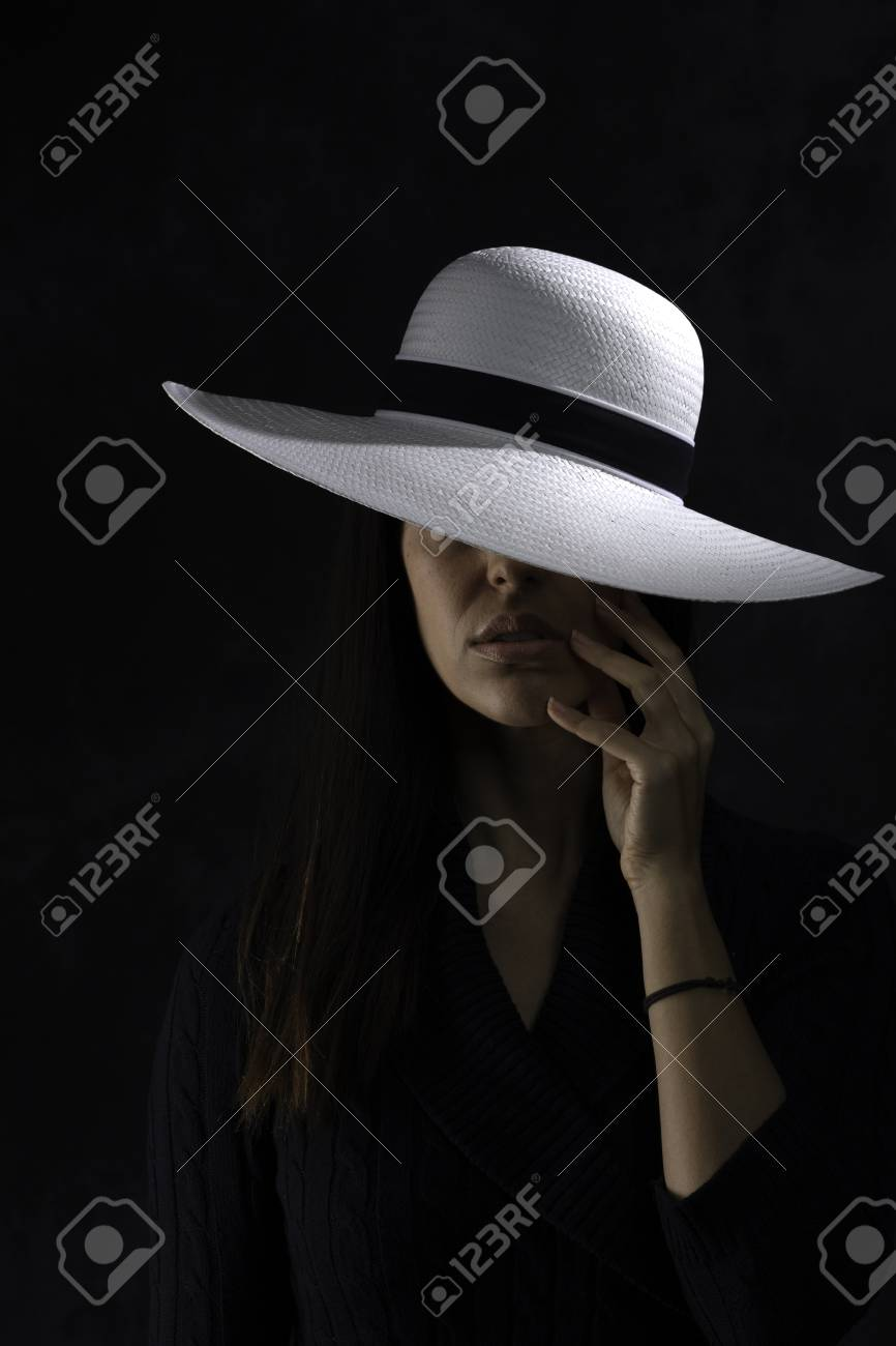 portrait of a beautiful young girl with a white hat on a black background, holding her hand under her chin - 126332864