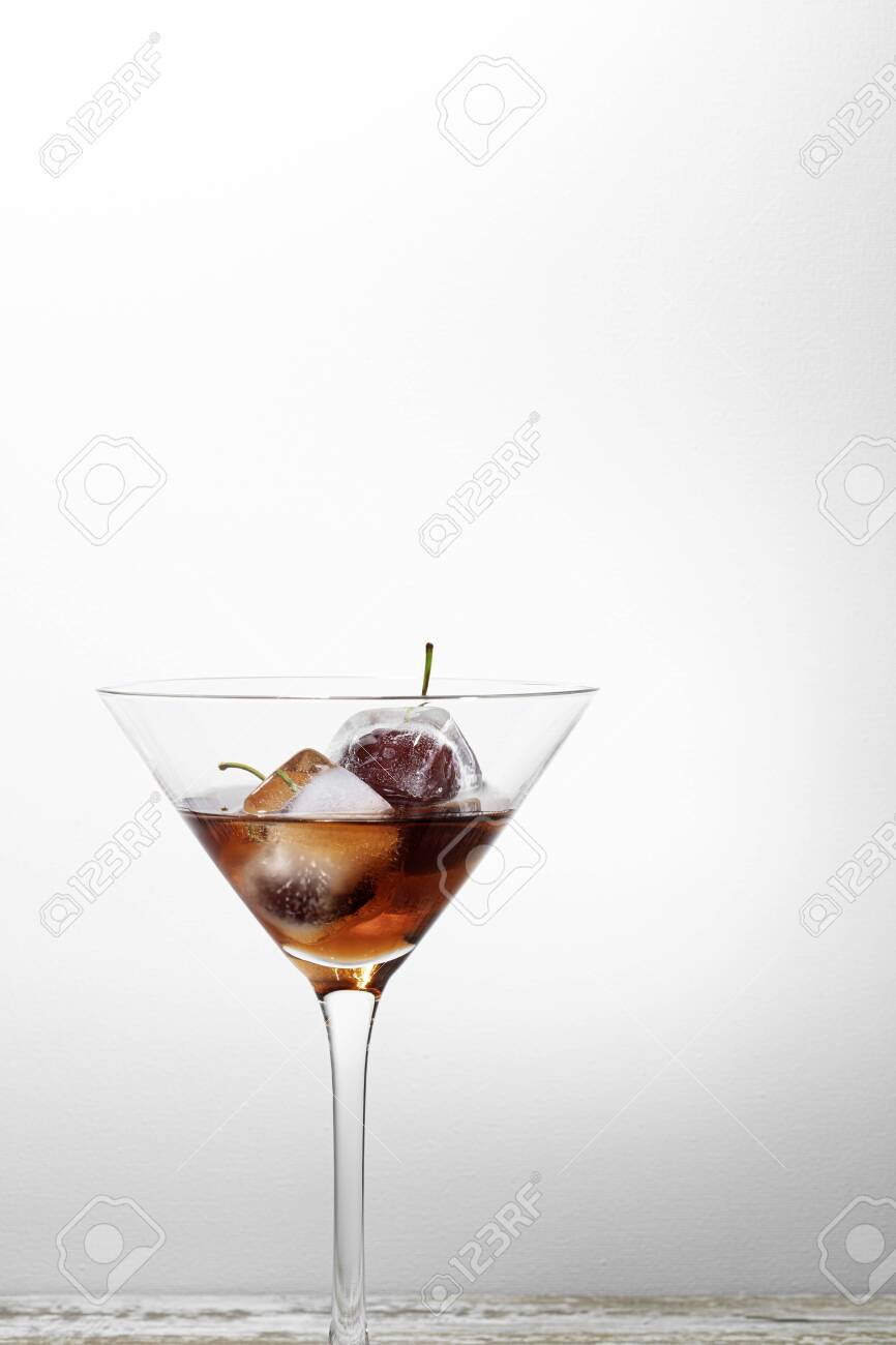 ice cubes with cherries inside into a red cocktail, white background textured with free space for text - 132005455