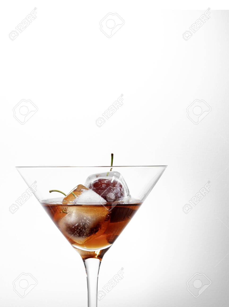 ice cubes with cherries inside into a red cocktail, white background with free space for text - 132005573