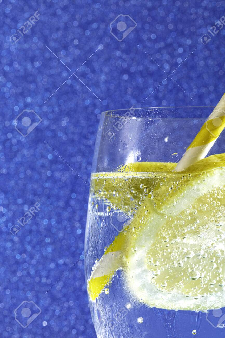 fresh soda with bubbles an ice cube, a slice of lemon and a straw on a shiny blue background - 132005758