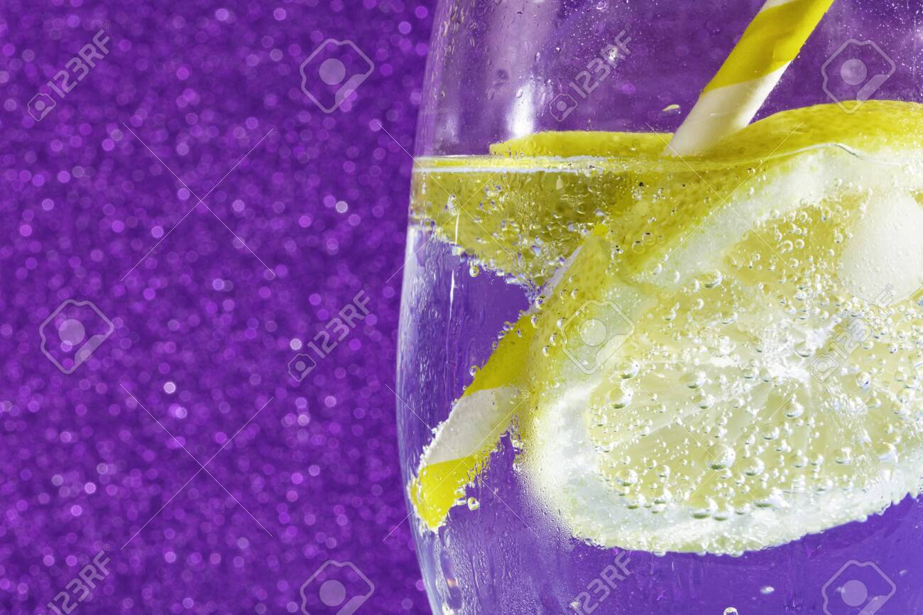 fresh soda with bubbles an ice cube, a slice of lemon and a straw on a shiny purple background. Free space for text - 132005554