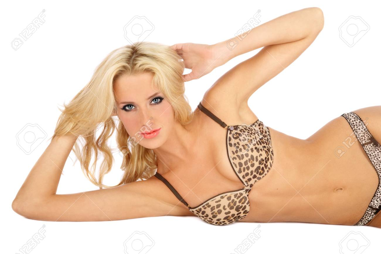 Beautiful sexy slim tanned blond girl in leopard print bra lying on white background Stock Photo - 5518647