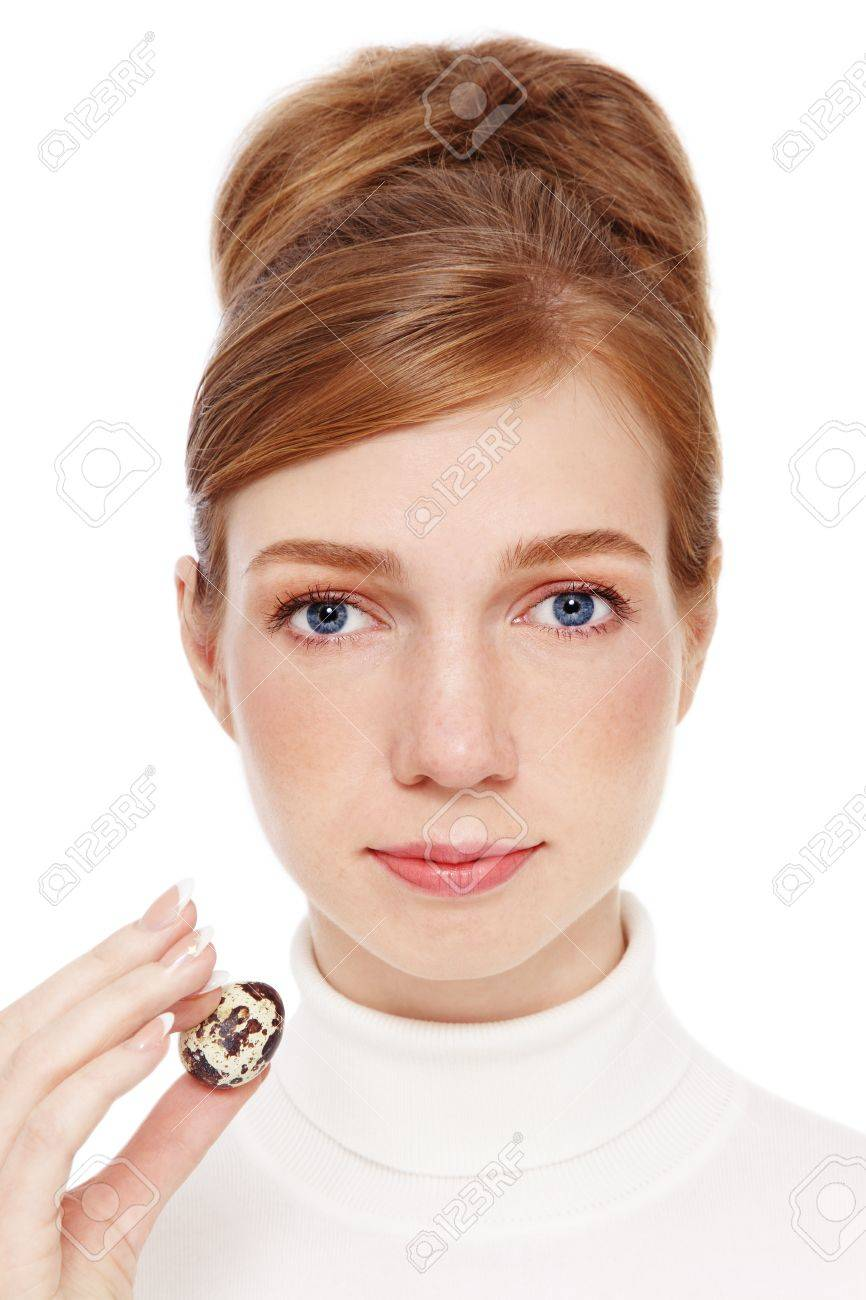 Young red-haired girl with freckles holding quail egg in her hand, on white background Standard-Bild - 16305625