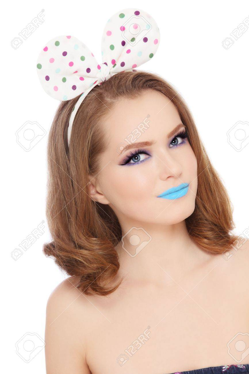 Pretty teen girl with fancy make-up and funny polka dot bow on her head looking upwards, white background Stock Photo - 16711476