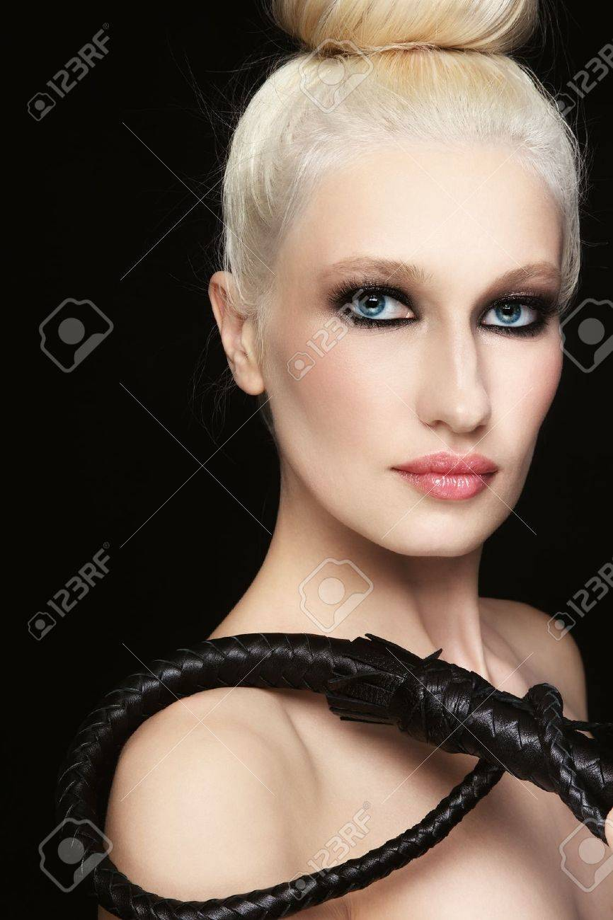 Young beautiful blond woman with braided bull whip in her hand Stock Photo - 16711469