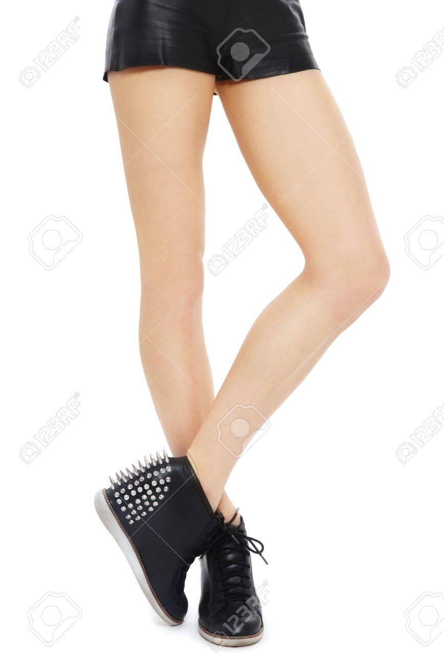 Beautiful legs of fit sexy woman in stylish spike boots and leather shorts, over white background Stock Photo - 17514607