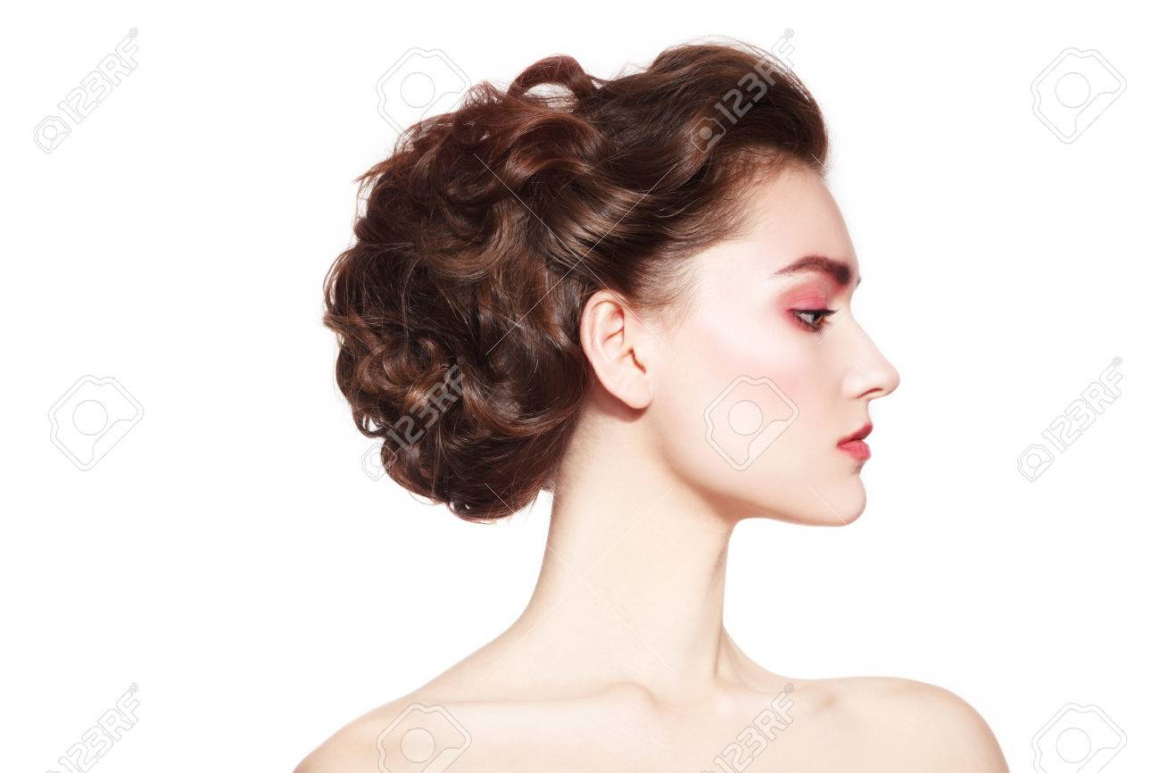 Profile portrait of young beautiful girl with stylish fresh make-up and prom hairdo over white background Banque d'images - 64600340