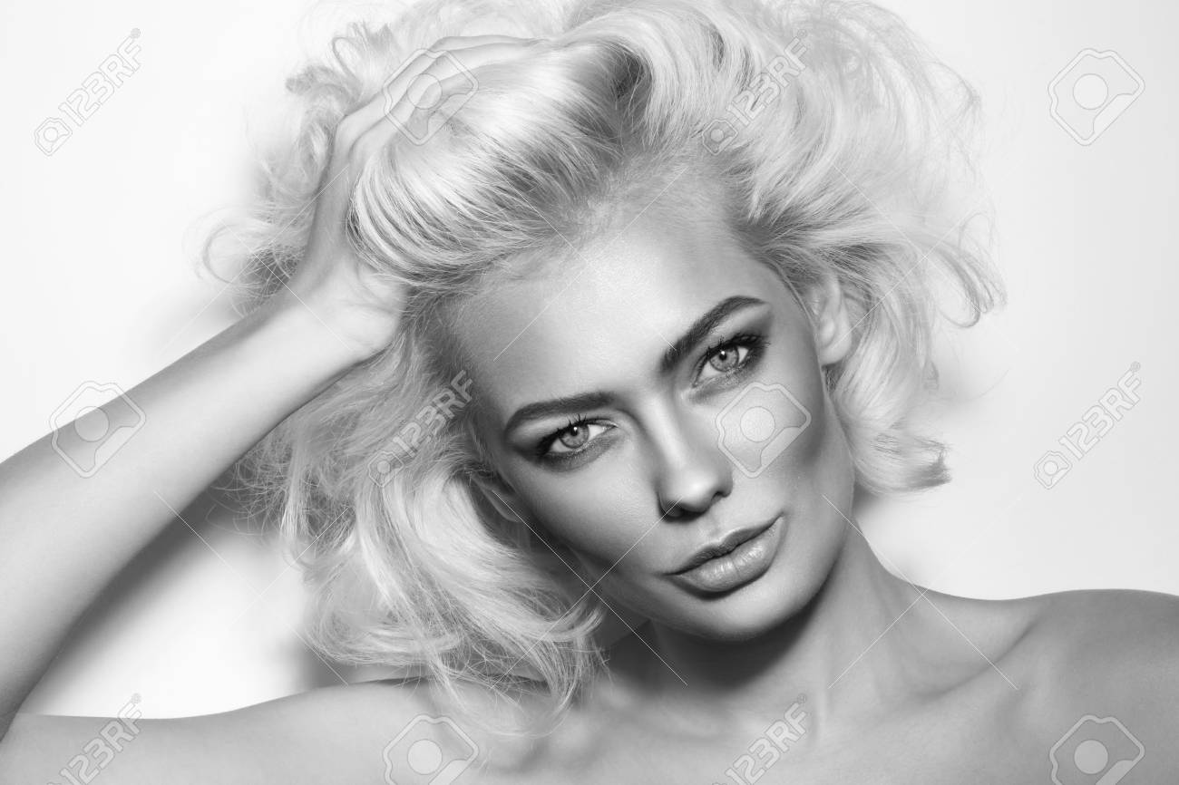 Black and white portrait of young beautiful glamorous woman with messy platinum blonde hair stock photo