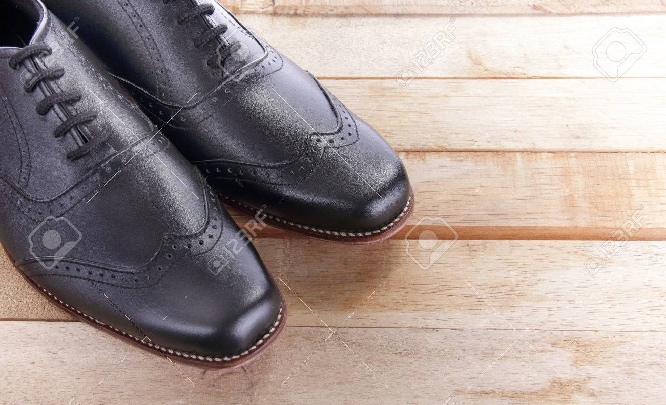 close up of a pair of leather shoes on top of wooden table stock
