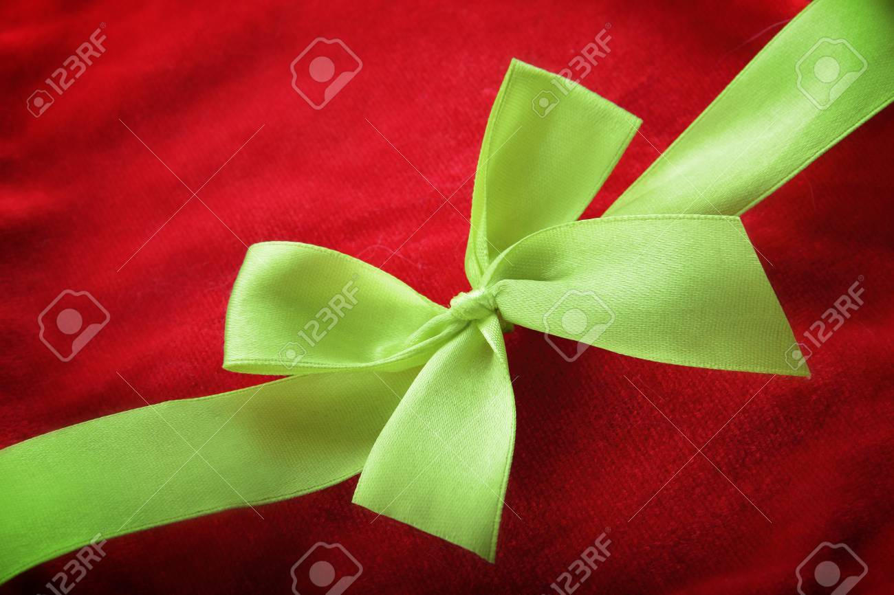 Close up of green ribbon crossing diagonally on red background
