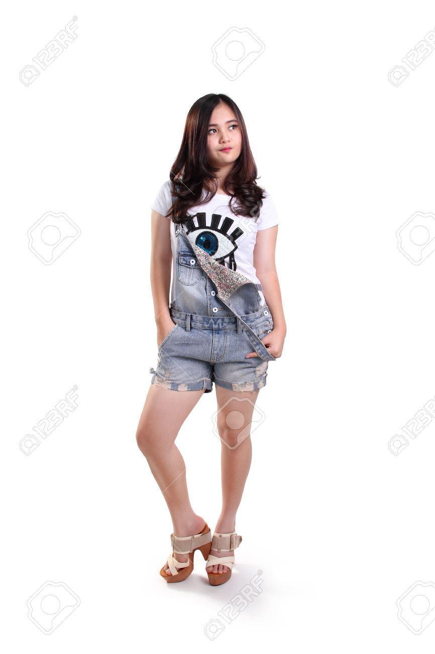 Full body pose of cool asian teenage girl standing over white studio background stock photo