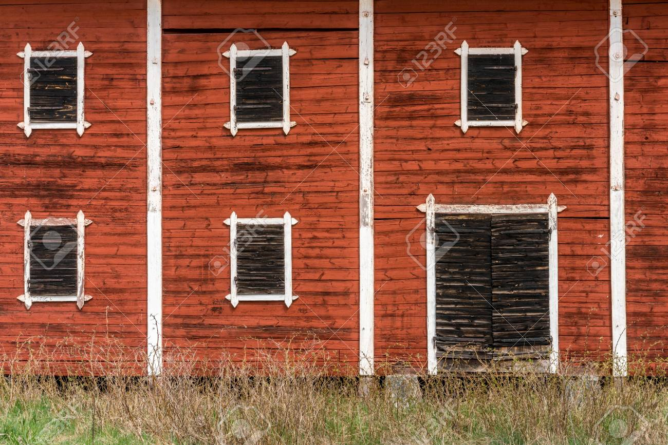 Exterior Of An Old Abandoned Decayed Red Barn With Closed Wooden