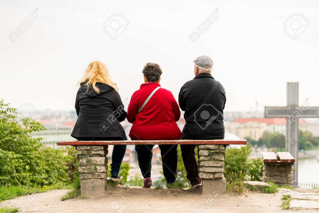 Back view of two woman and one elderly man sitting on a bench looking out over Budapest Hungary. Stock Photo - 87993832