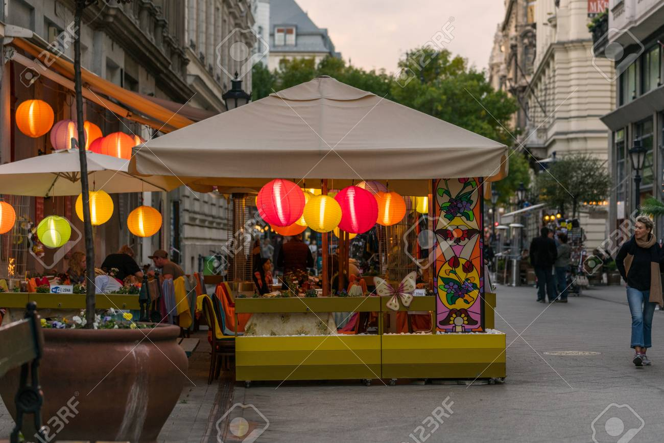 Budapest, Hungary - September 25, 2017: Street view of people in outdoor restaurant with colored rice lamps eating dinner. Pedestrian street Vaci utca in Budapest Hungary with incidental people walking by. Stock Photo - 87197845