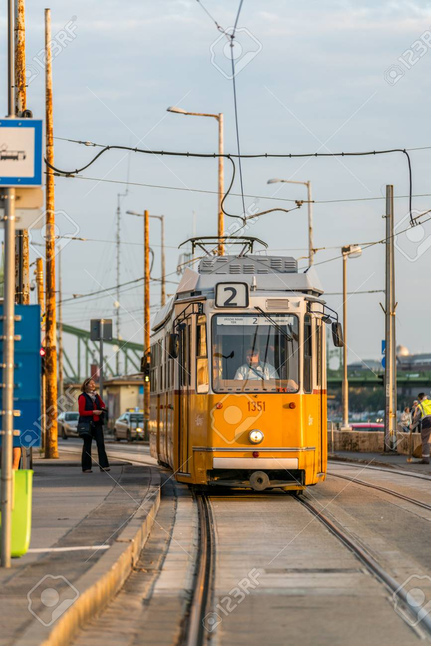 Budapest, Hungary - September 25, 2017: Close up front view of a yellow tram approaching a tram stop in Budapest Hungary to pick up passengers. Male tram driver looking through window and a female passenger about to enter the tram. Incidental people in th Stock Photo - 87197848