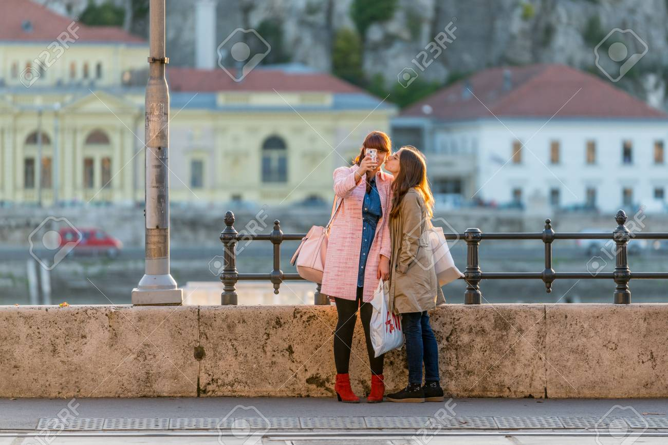 Budapest, Hungary - September 25, 2017: Close up sunset front view of two young caucasian woman with shopping bags by a steel railing in Budapest Hungagry. Using a mobile phone to take a selfie while giving a kiss, the Danube river and buildings in the ba Stock Photo - 87197849
