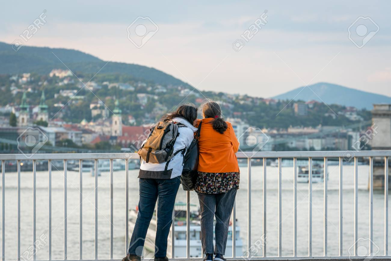 Budapest, Hungary - September 25, 2017: Close up back view of two caucasian woman talking and leaning against a steel railing on a bridge in Budapest Hungary. Enjoying the view of the city and boats on the Danube river in the background. Stock Photo - 87197850